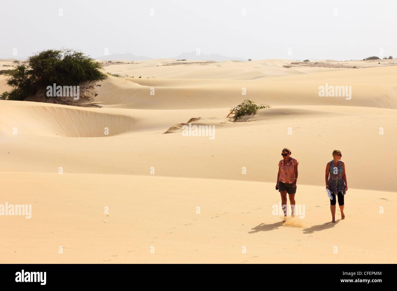 View of two women tourists walking barefoot on hot empty desert sand dunes. Deserto de Viana, Boa Vista, Cape Verde Stock Photo