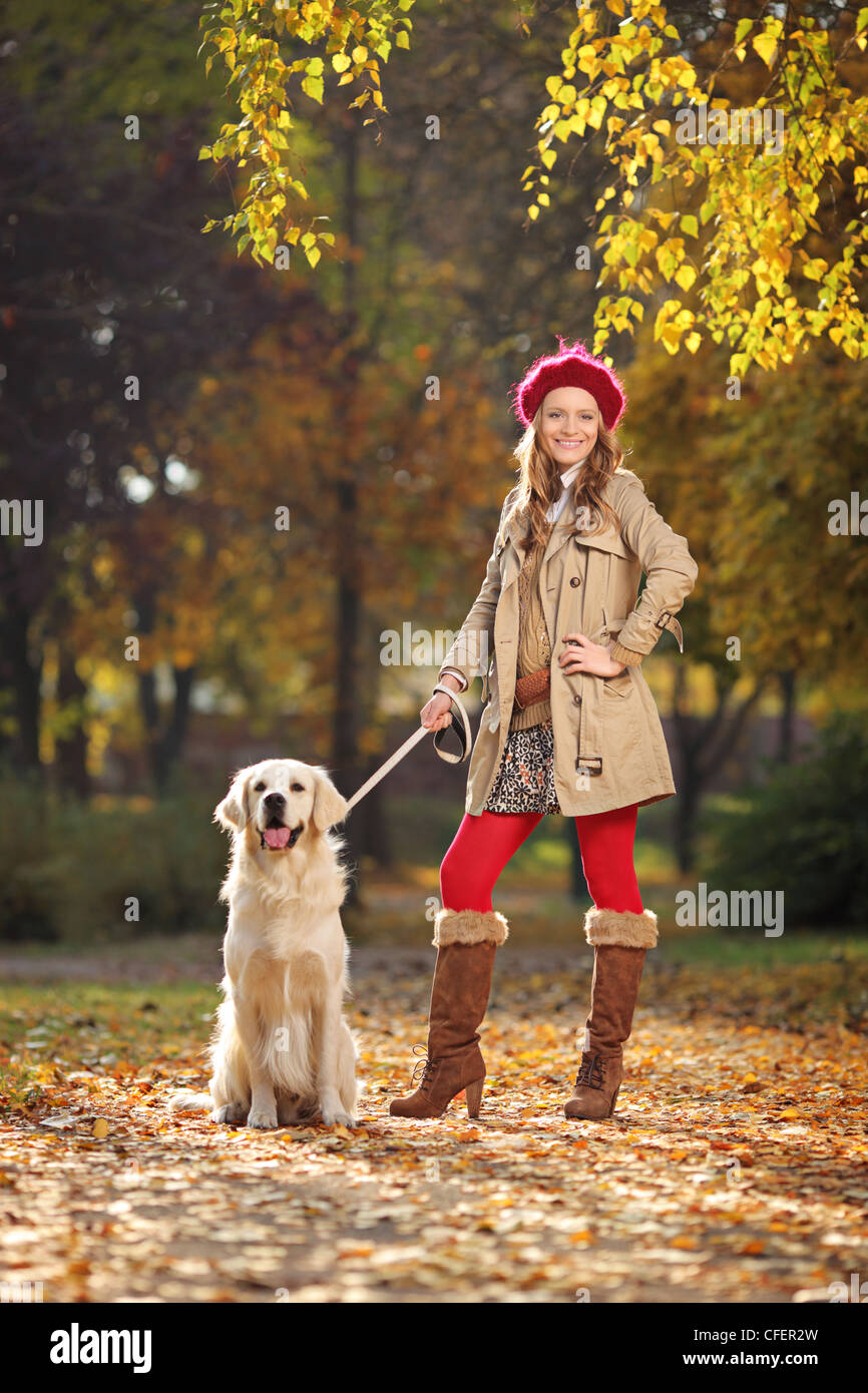 Smiling young woman with her labrador retreiver dog in a city park - Stock Image
