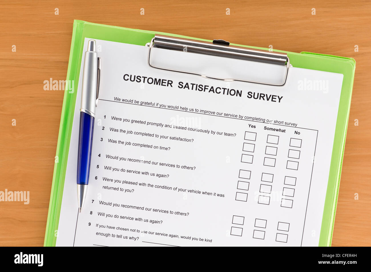 Customer satisfaction survey with pen on green clipboard - Stock Image