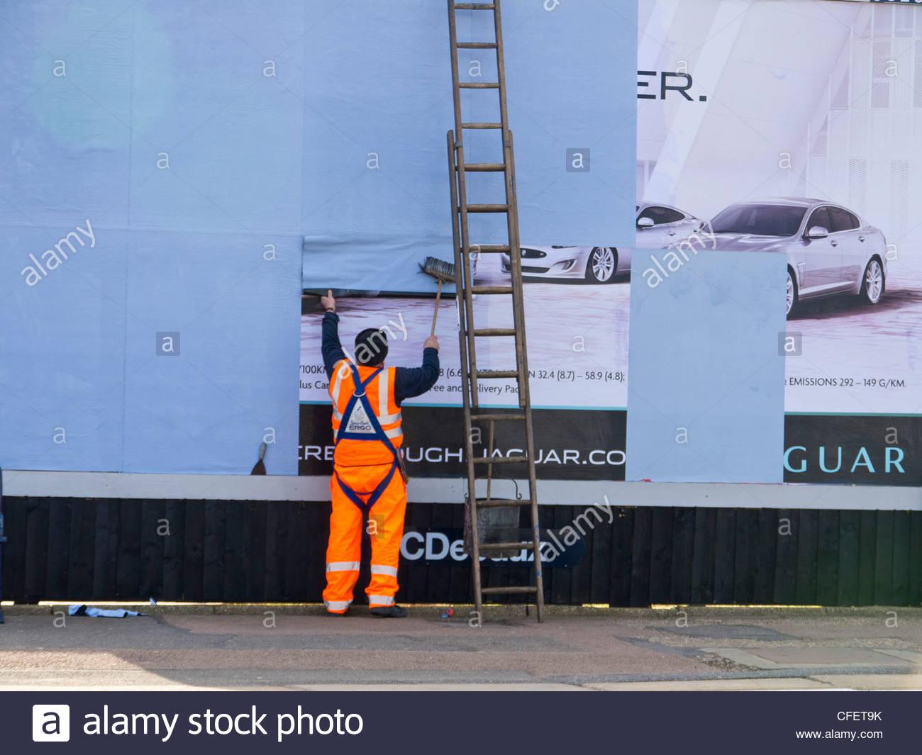 https://c8.alamy.com/comp/CFET9K/bill-poster-pasting-ad-on-ladder-england-uk-CFET9K.jpg