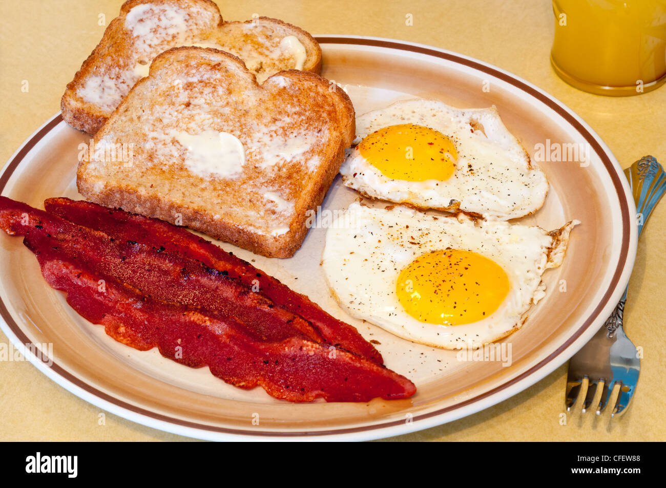 Simple Breakfast Of Fried Eggs Bacon Toast And Juice