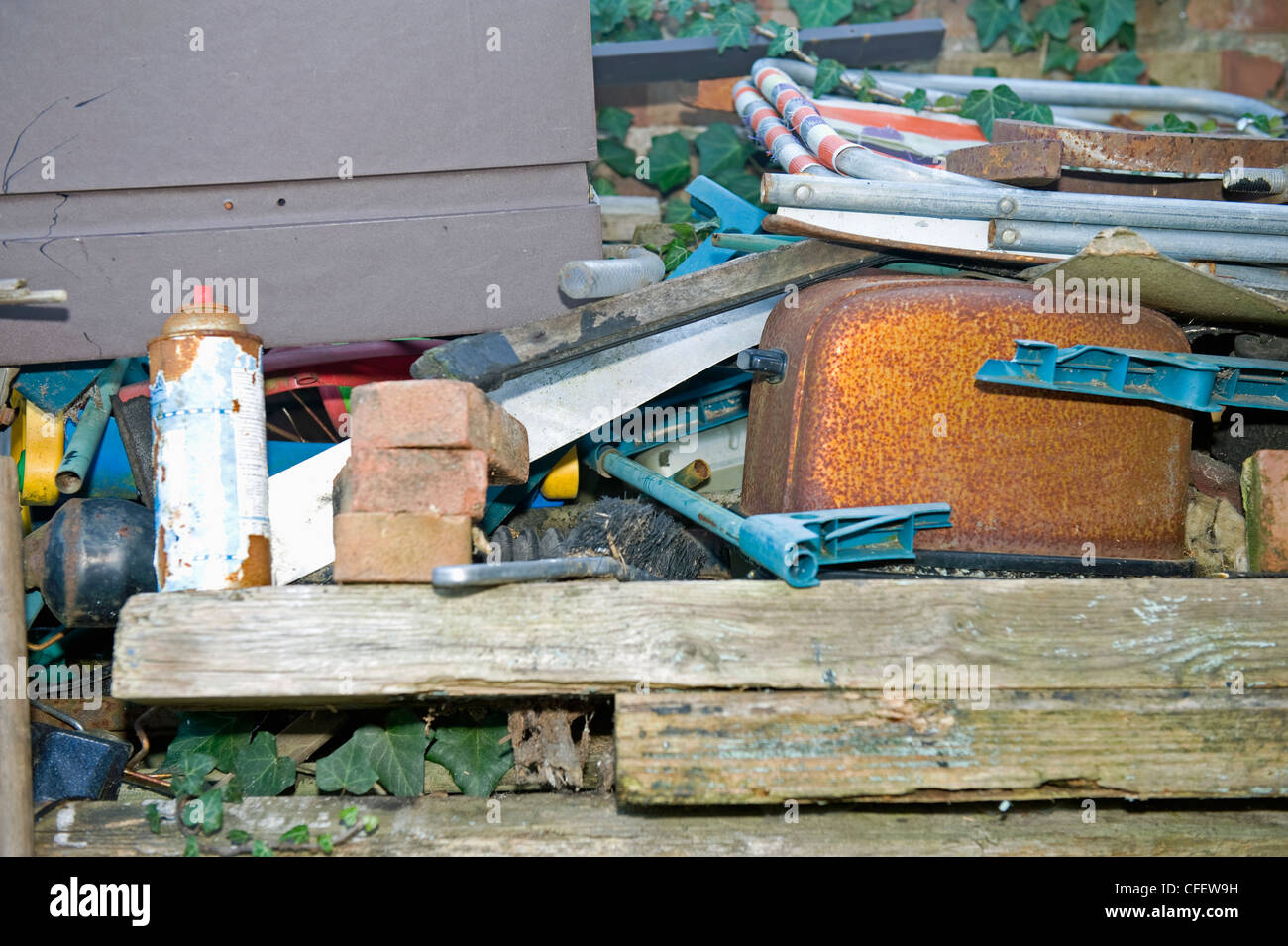 An old rusted toaster in amongst a pile of junk in a back garden. - Stock Image
