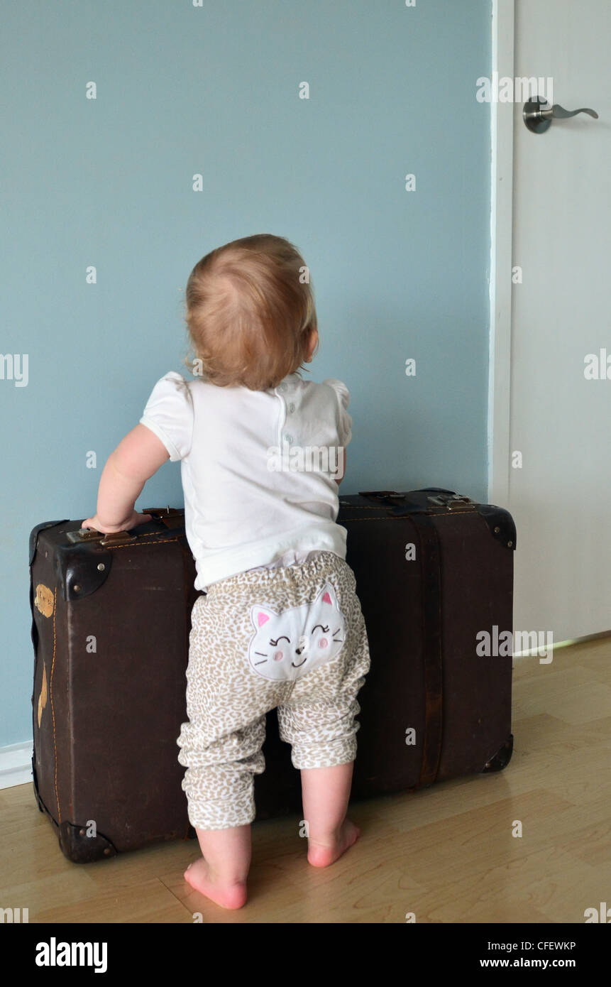 Toddler holding a suitcase - concept photo - leaving home at a young age Stock Photo