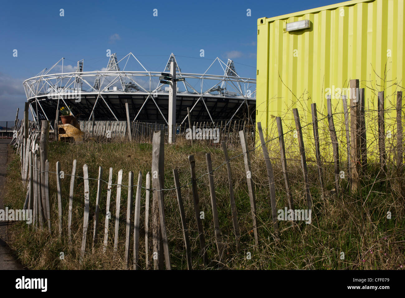 Incongruous landscape of bygone era fencing, shipping container and new 2012 Olympic stadium on Stratford Greenway - Stock Image