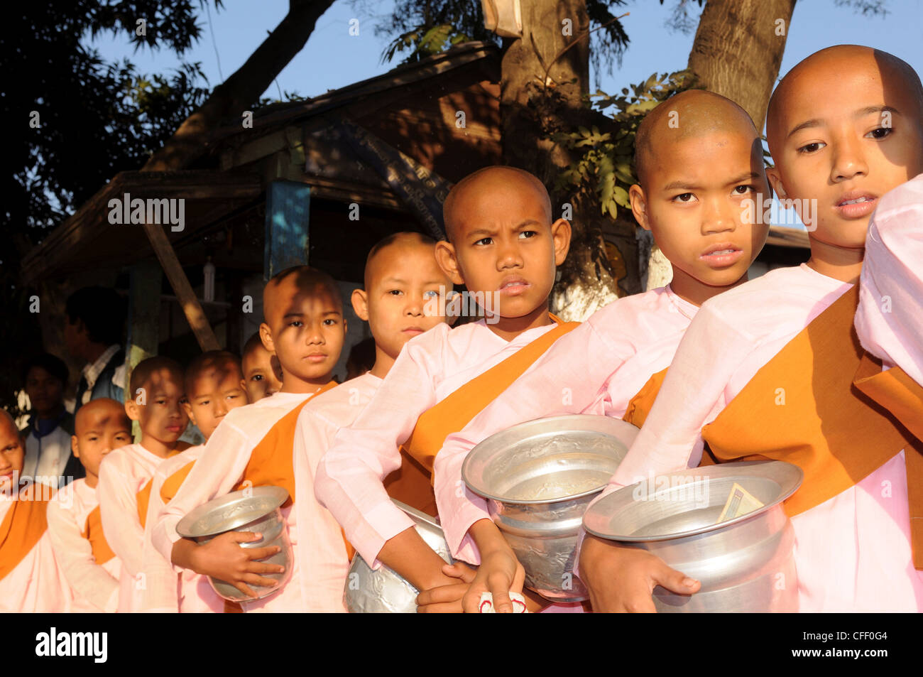 Young female monks waiting to receive rice from donors, Pyay, Myanmar, Asia - Stock Image