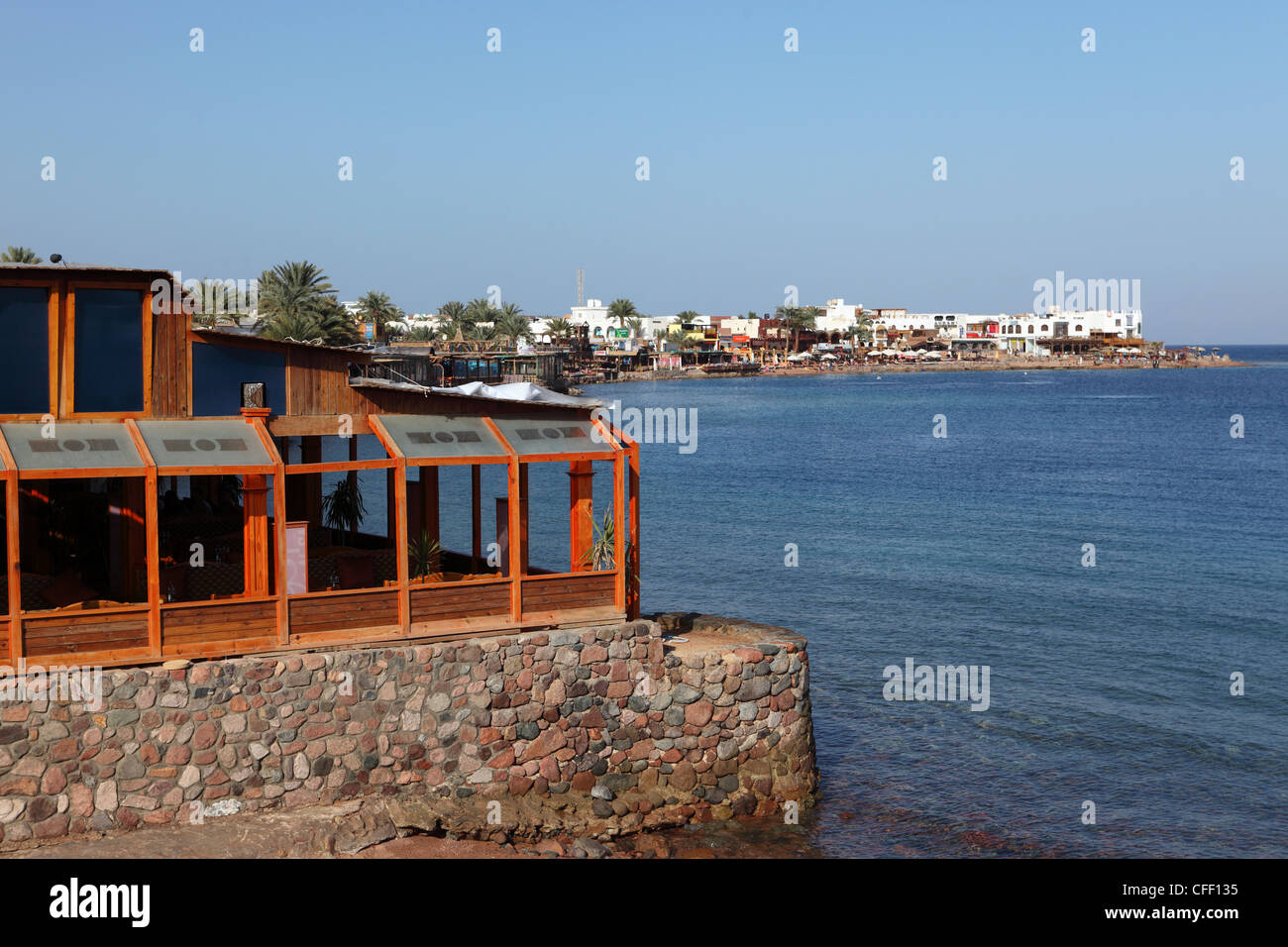 A restaurant overlooks the harbour of the Red Sea resort town of Dahab in Egypt, North Africa, Africa - Stock Image