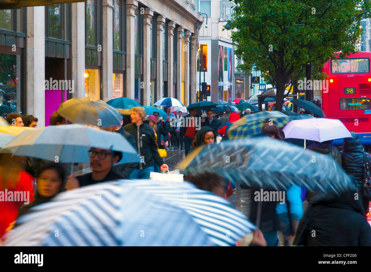 Shoppers in the rain, Oxford Street, London, England, United Kingdom, Europe - Stock Image