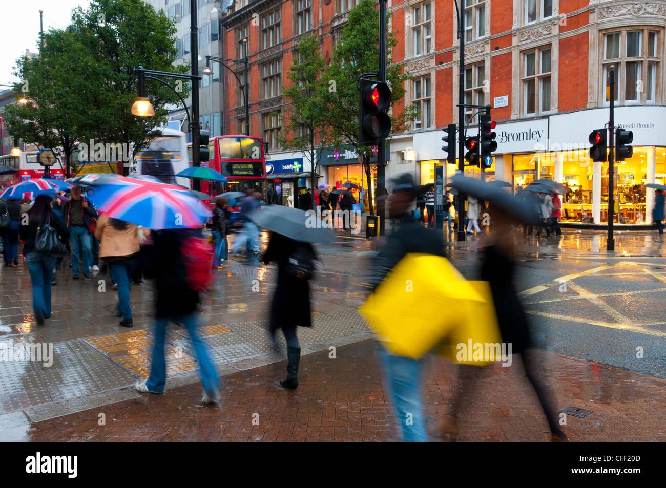 Shoppers in the rain, Oxford Street, London, England, United Kingdom, Europe - Stock Image