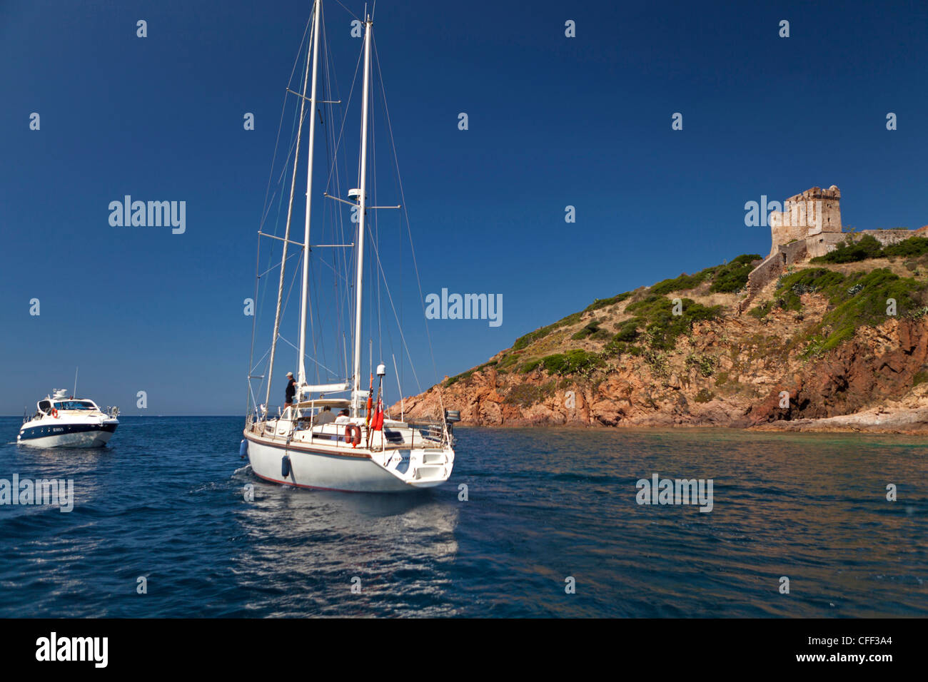 Boat anchored by a Genoese Tower, village of Girolata, Corsica, France - Stock Image