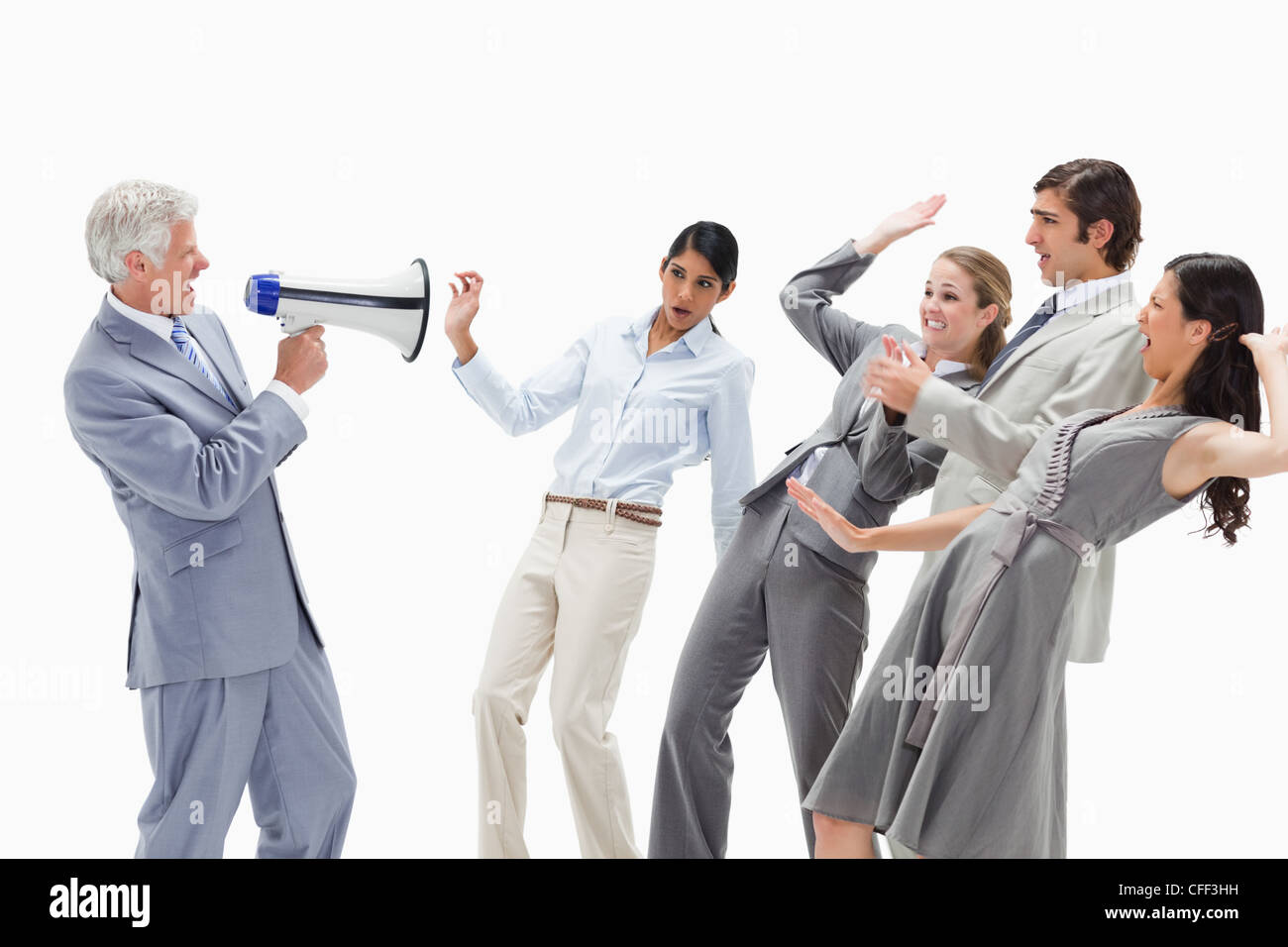 Man yelling in a megaphone at stunned business people - Stock Image