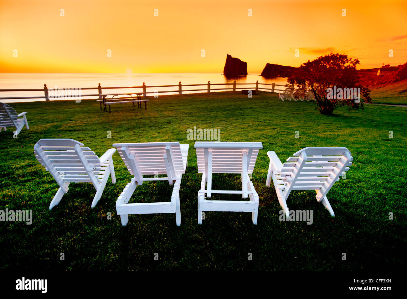 Lawn chairs and Perce Rock at sunrise, Perce, Gaspé Penninsula, Quebec, Canada - Stock Image