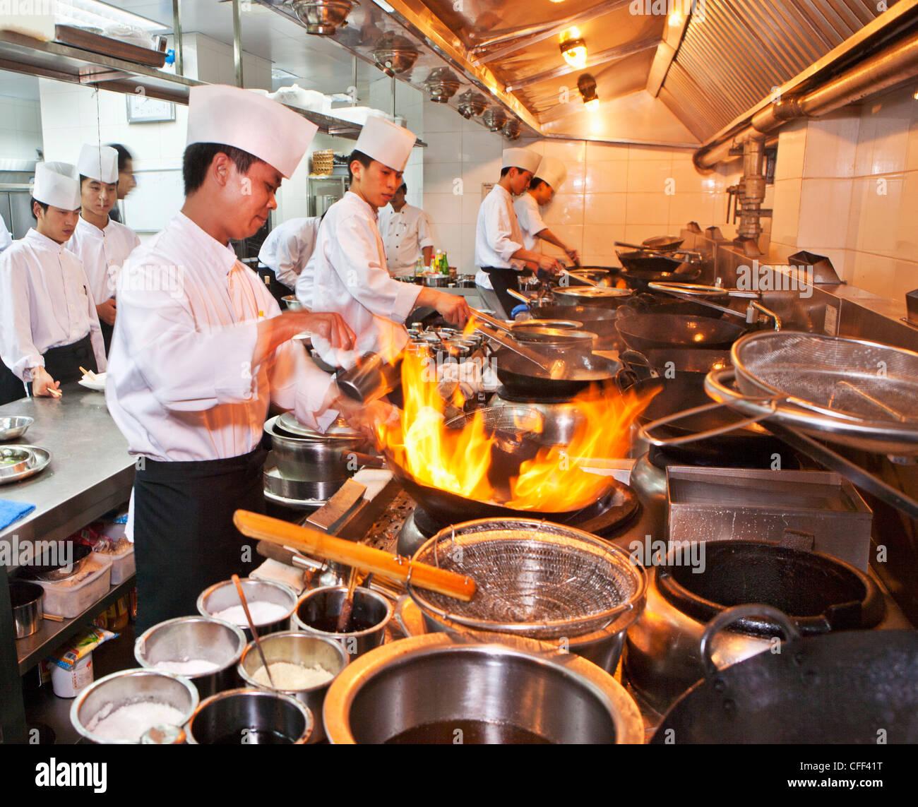 Chefs Preparing Chinese Cuisine In Woks In The Modern