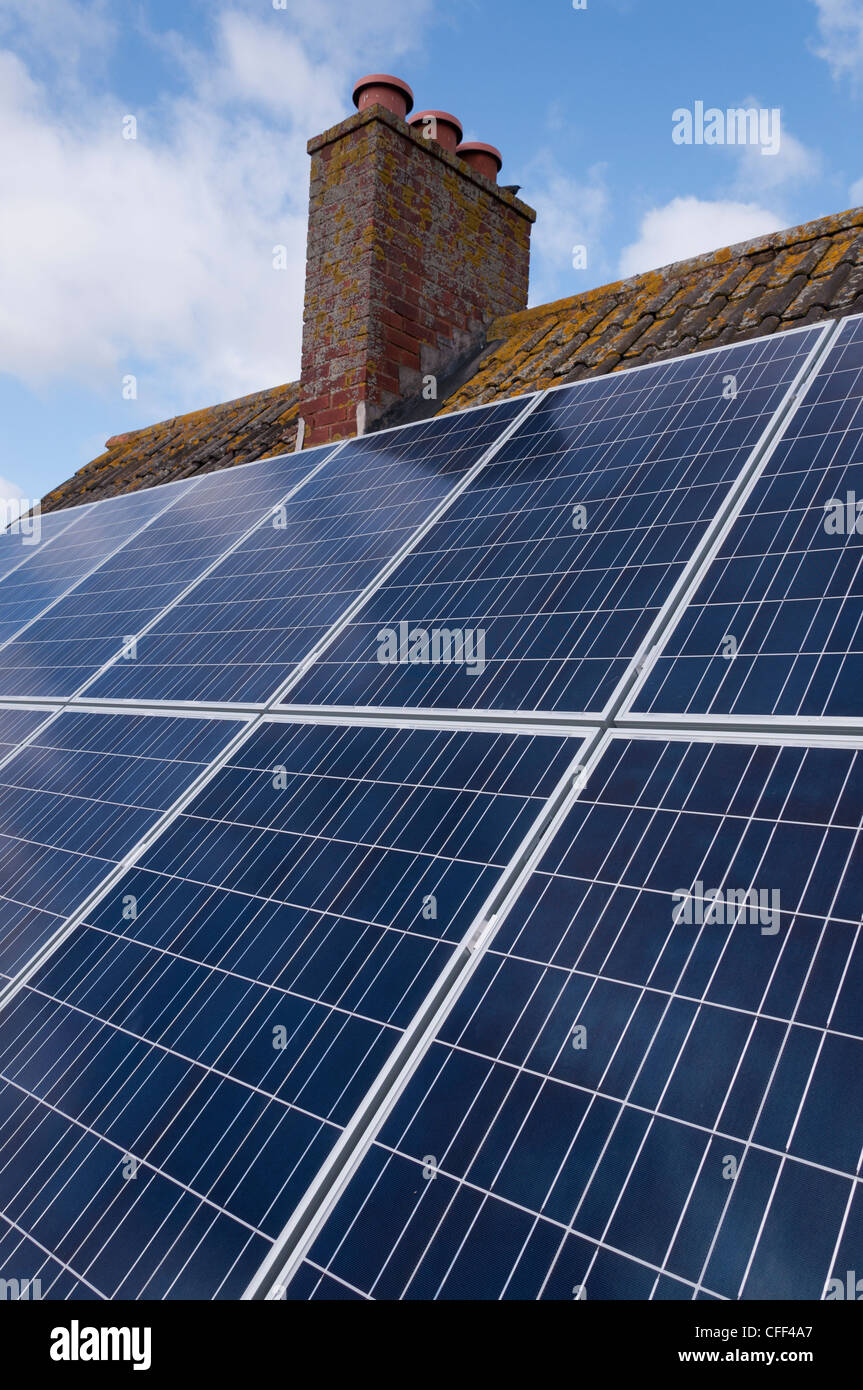 Solar panels fitted to the tiled roof of a UK home. - Stock Image