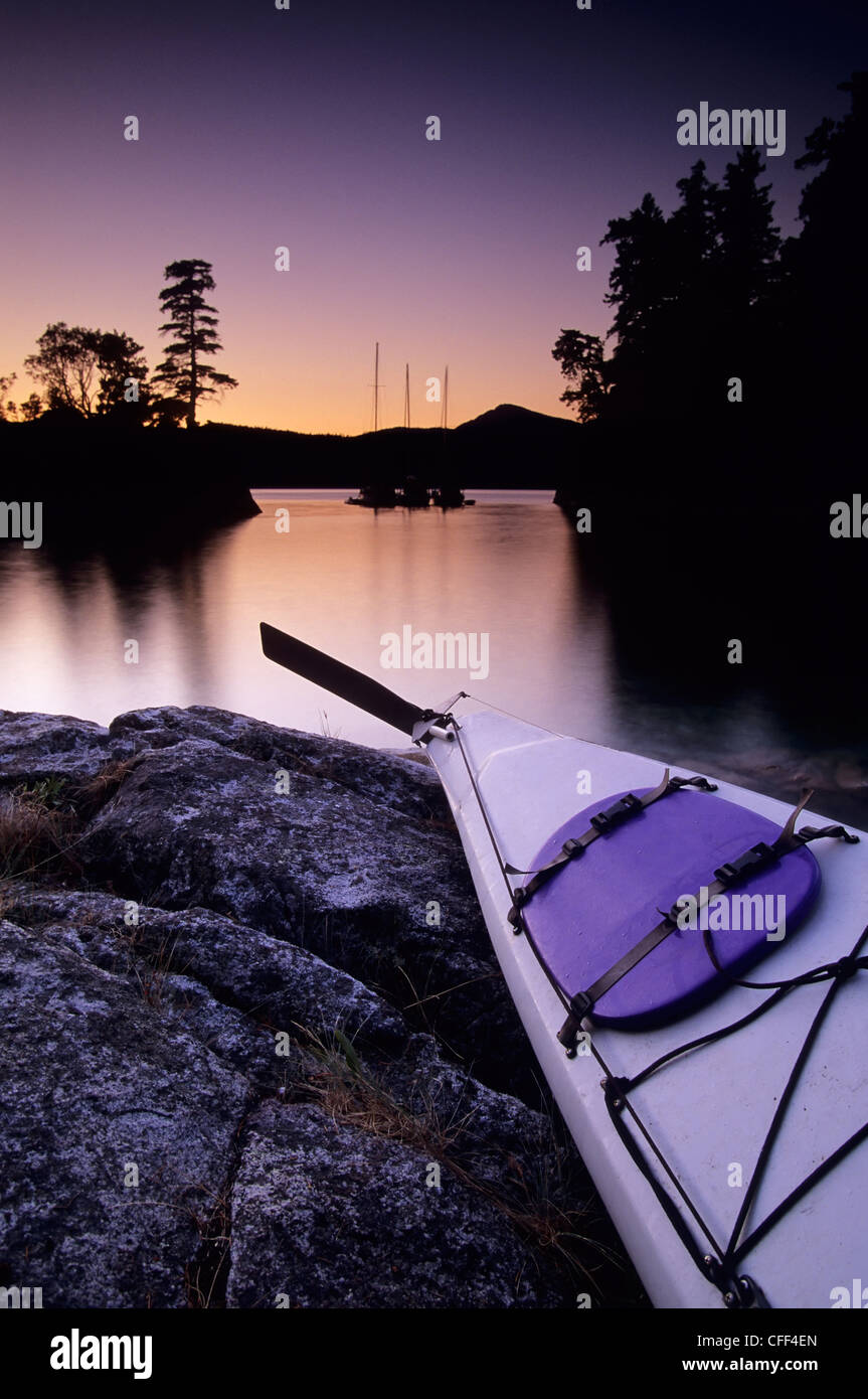 Kayak and Yachts at dusk in Desolation Sound Marine Park, Curme Island, British Columbia, Canada. - Stock Image