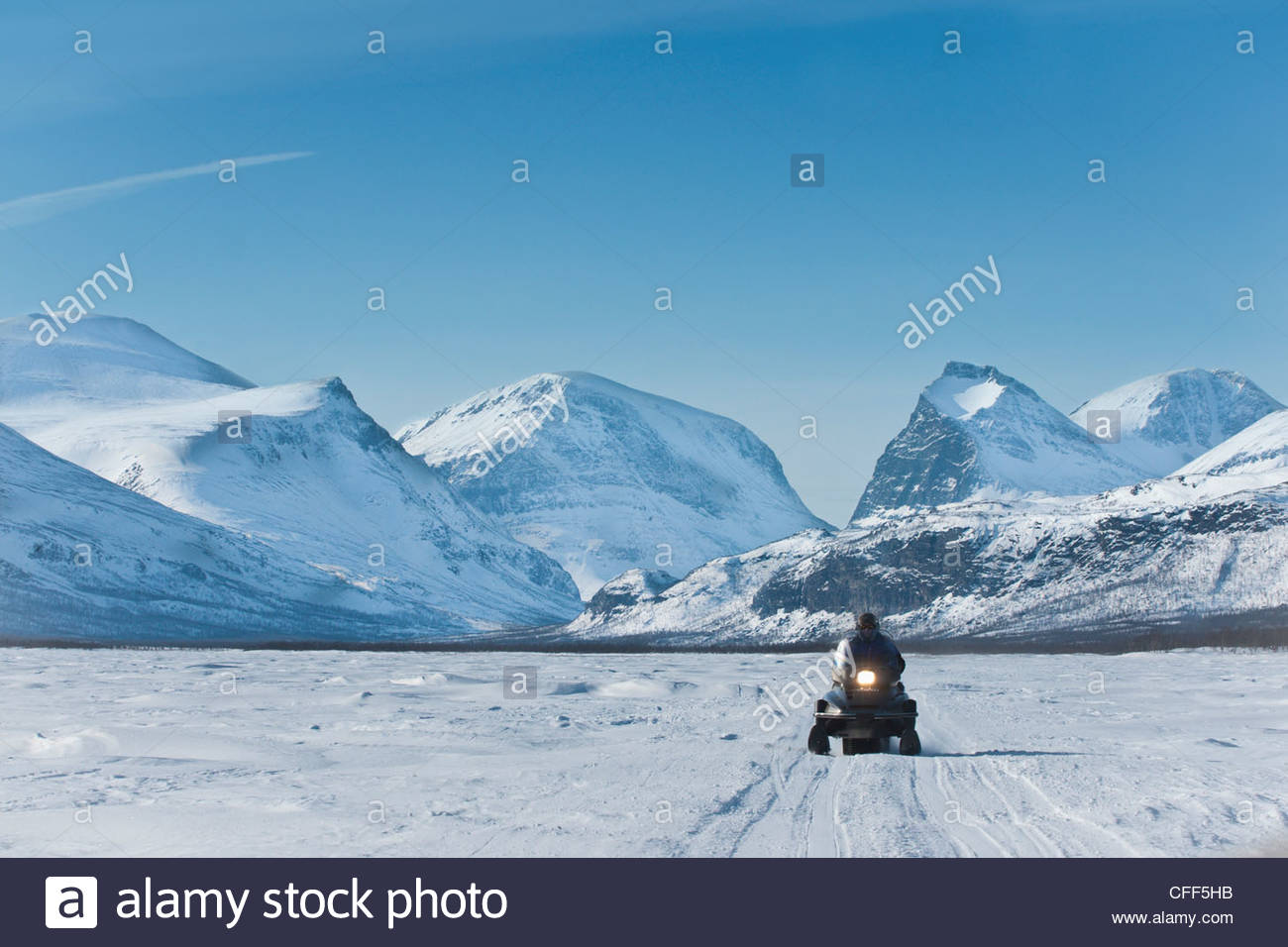 Snowmobiling in Kalix river valley with snow covered mountains, Kiruna region, arctic Sweden, Scandinavia, Europe - Stock Image