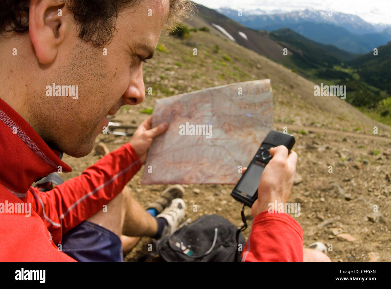 Mountain biker checks the map with a GPS unit in Windy Pass, Southern Chilcotin Mountains, British Columbia, Canada. Stock Photo