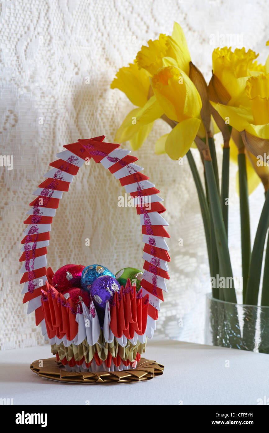 Origami Basket With Mini Easter Eggs In And Daffodils Behind Stock