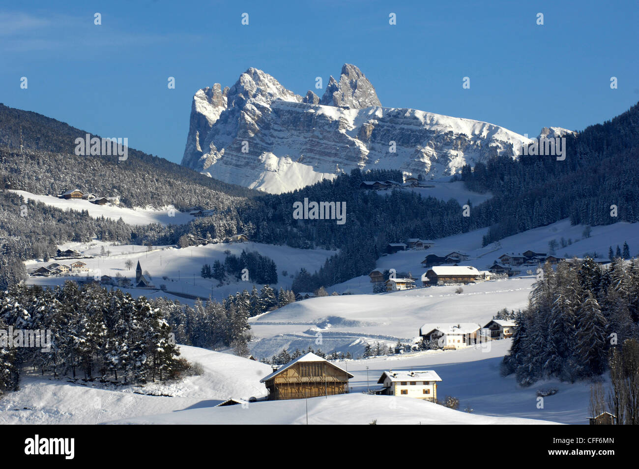 Farmhouses in snowy landscape in front of Geisler mountain range, Kastelruth, Valle Isarco, Alto Adige, South Tyrol, - Stock Image