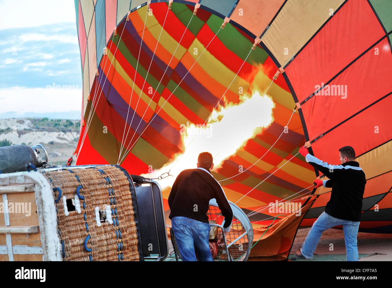Firing up the balloon for the nest batch of tourists in Cappadocia - Stock Image