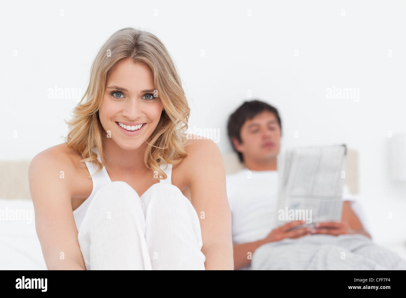 Woman at the bottom of the bed smiling as the man reads at the top of the bed - Stock Image