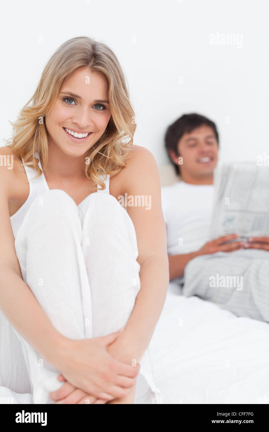 Close up, Woman sitting at the bottom of the bed, with the man at the top reading - Stock Image