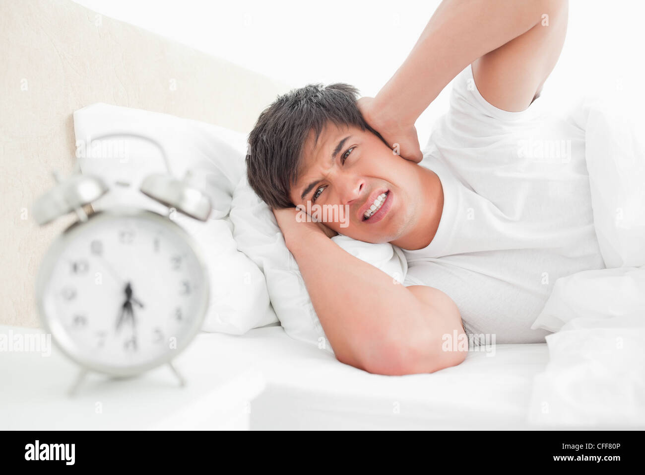 Man covering his ears as his alarm clock rings loudly - Stock Image