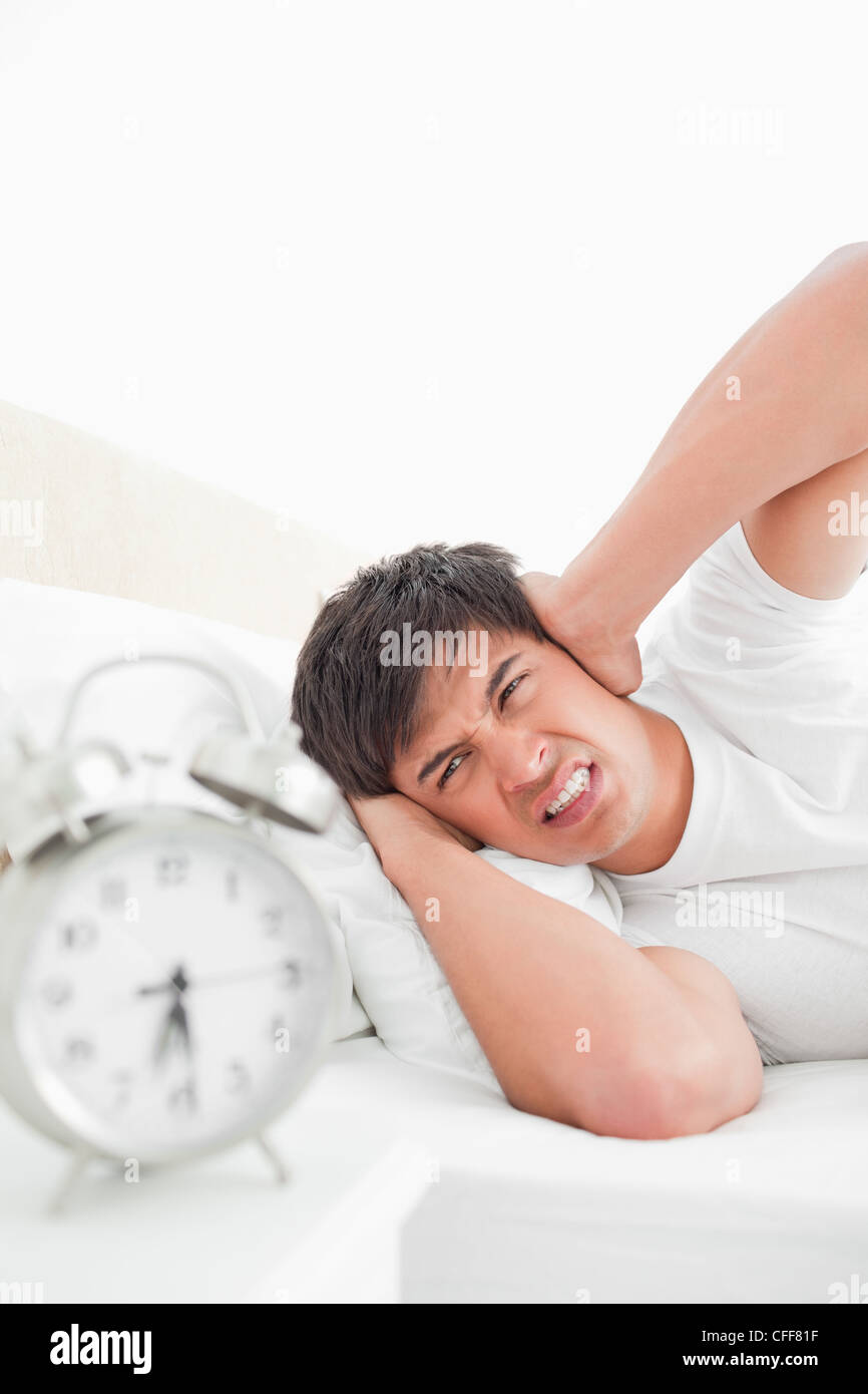 Man covering his ears in anger as the alarm clock rings loudly - Stock Image