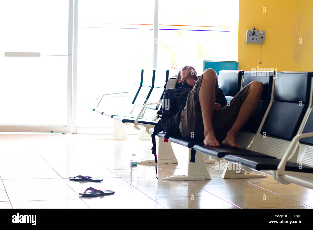 An exhausted male traveler waits in an airport terminal for his flight to arrive at the Manzanillo International - Stock Image