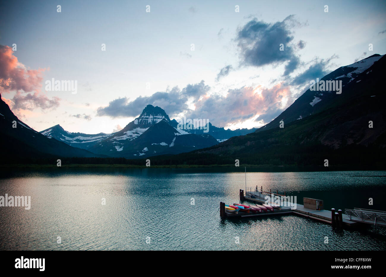 A lake with a dock and kayaks at dusk in a national park. - Stock Image