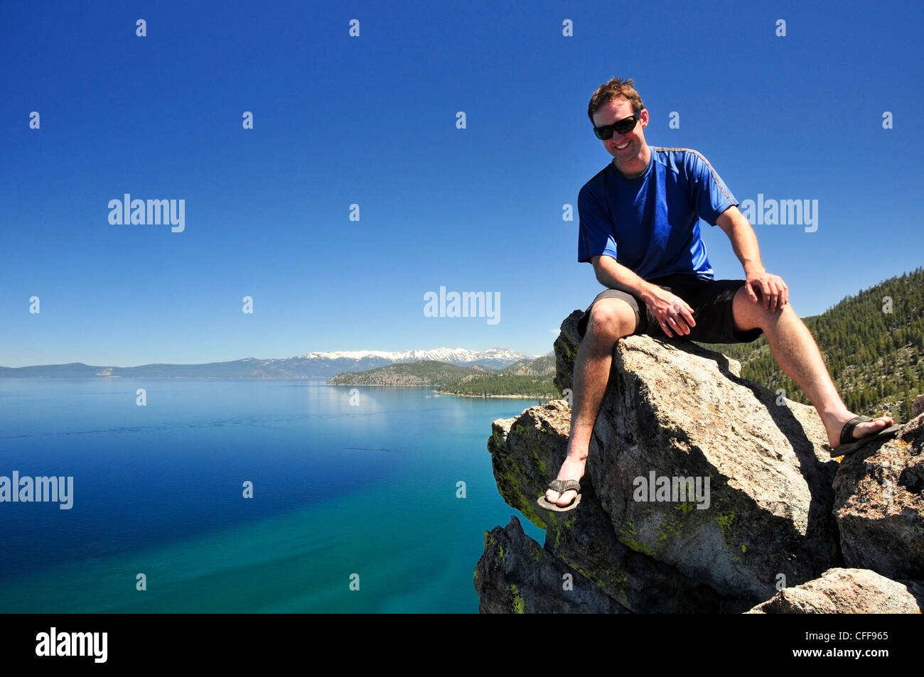 A man relaxes on a boulder overlooking Lake Tahoe in the summer, Nevada. - Stock Image