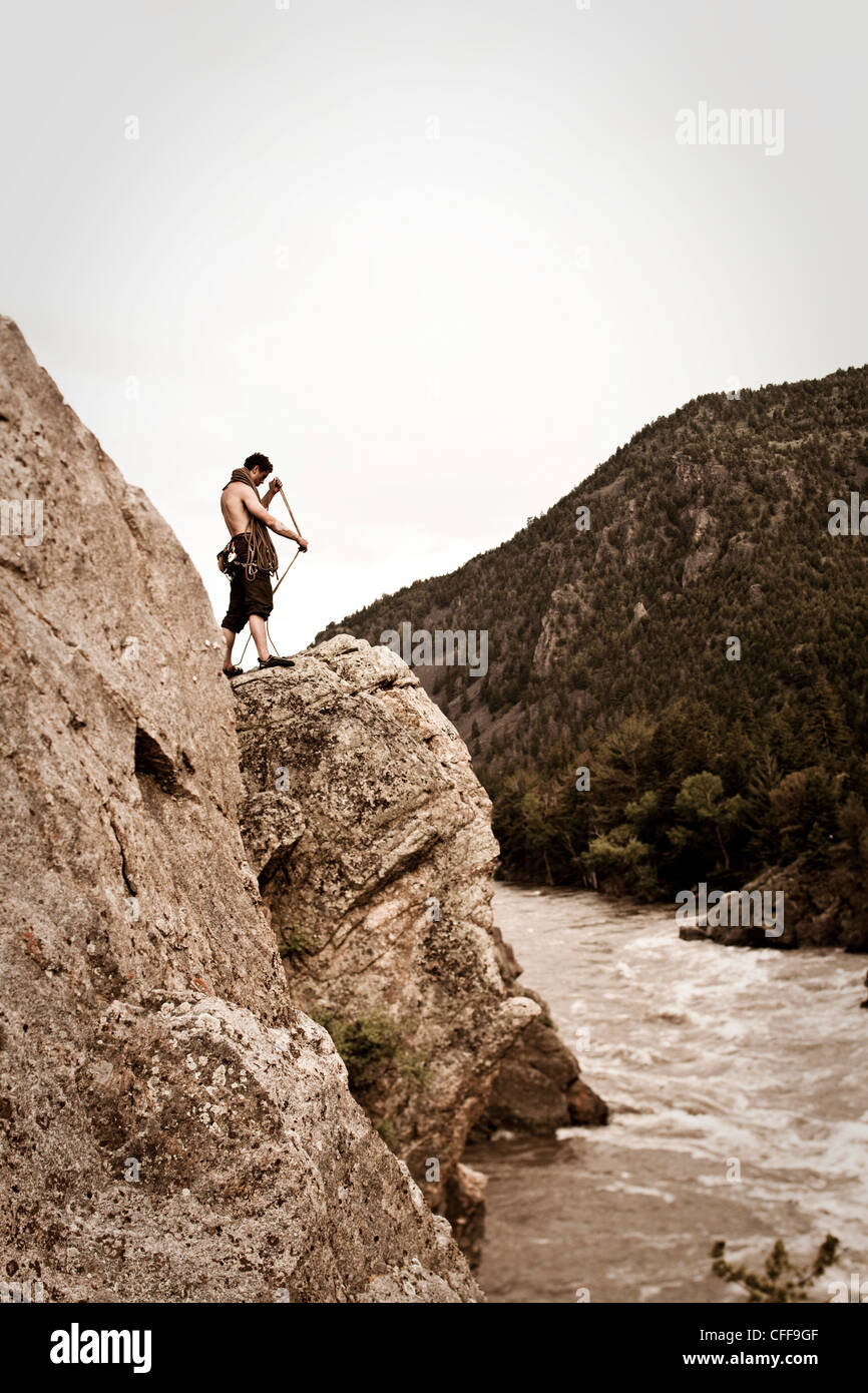 A athletic man coils a rock climbing rope next to a river in Montana. - Stock Image