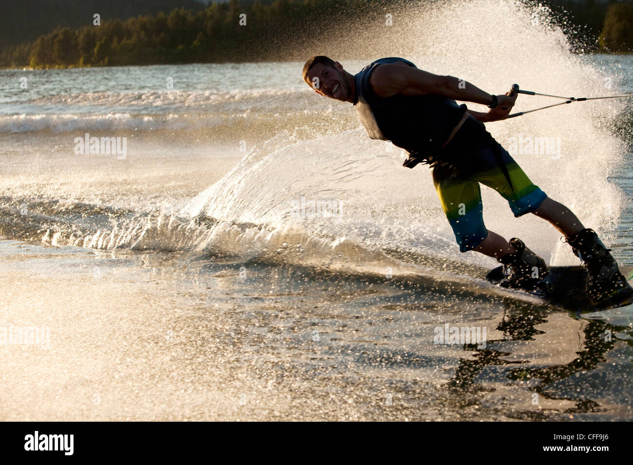 A professional wakeboarder smiles while he carves and slashes on Lake Pend Oreille at sunset in Sandpoint, Idaho. - Stock Image