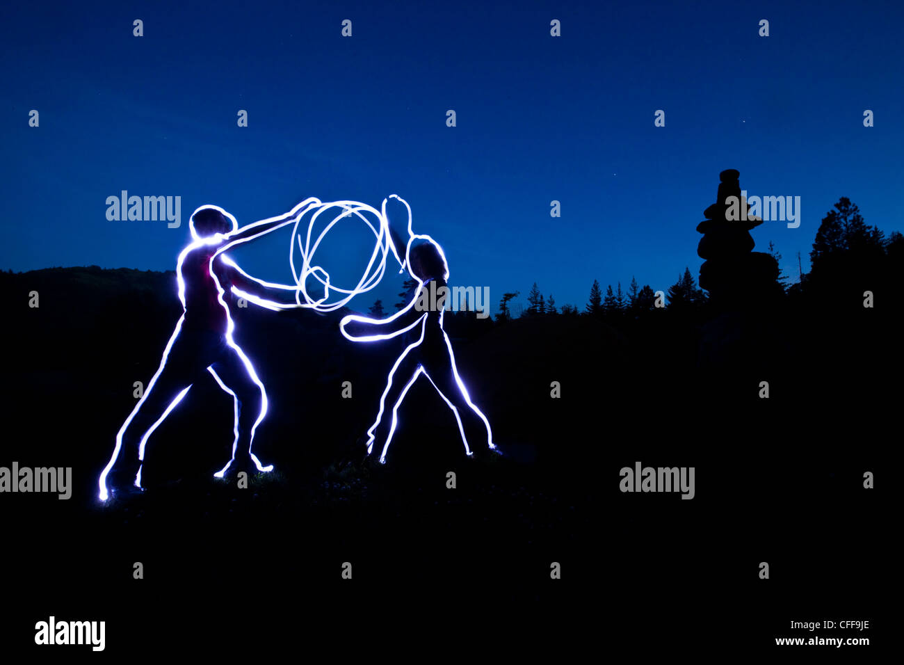 A light painting of two figures holding a ball of light energy at sunset in Idaho. - Stock Image