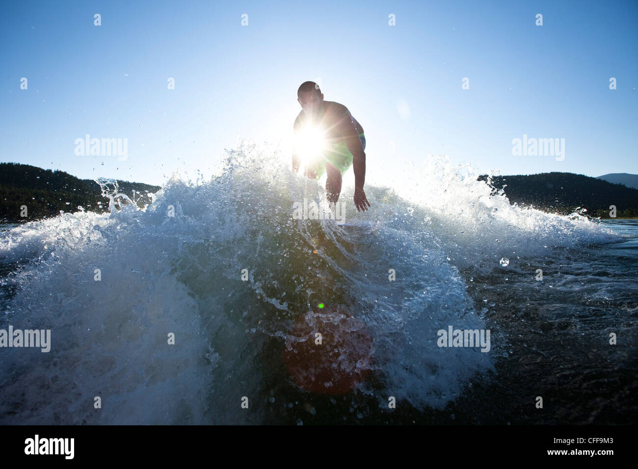 A athletic male surfing behind a wakeboard boat at sunset in Idaho. - Stock Image