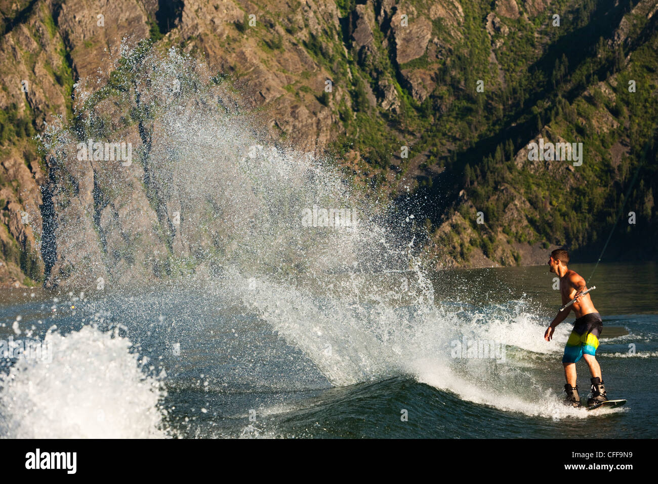 A athletic male wakeboarder carves and slahes the wake at sunset on a lake in Idaho. - Stock Image
