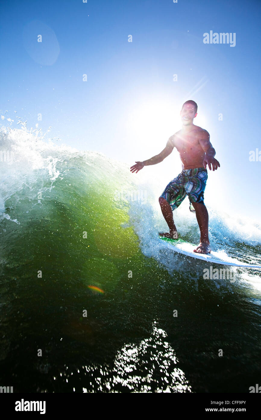 A athletic male surfing behind a wakeboard boat on a lake in Idaho. - Stock Image