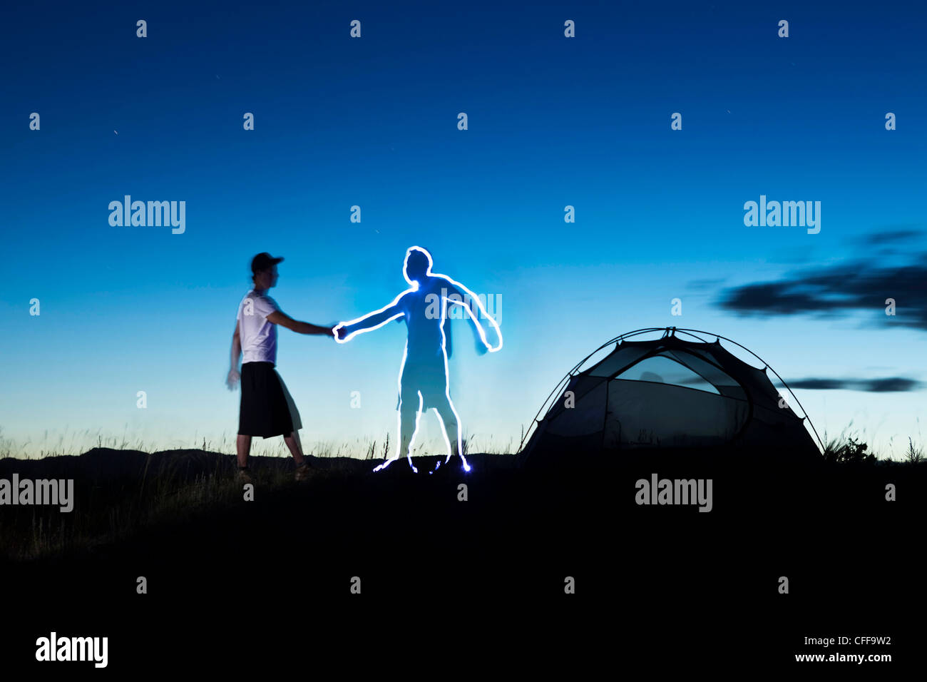 A light painting of a man shaking the hand of a digital friend on a camping trip in Montana. - Stock Image
