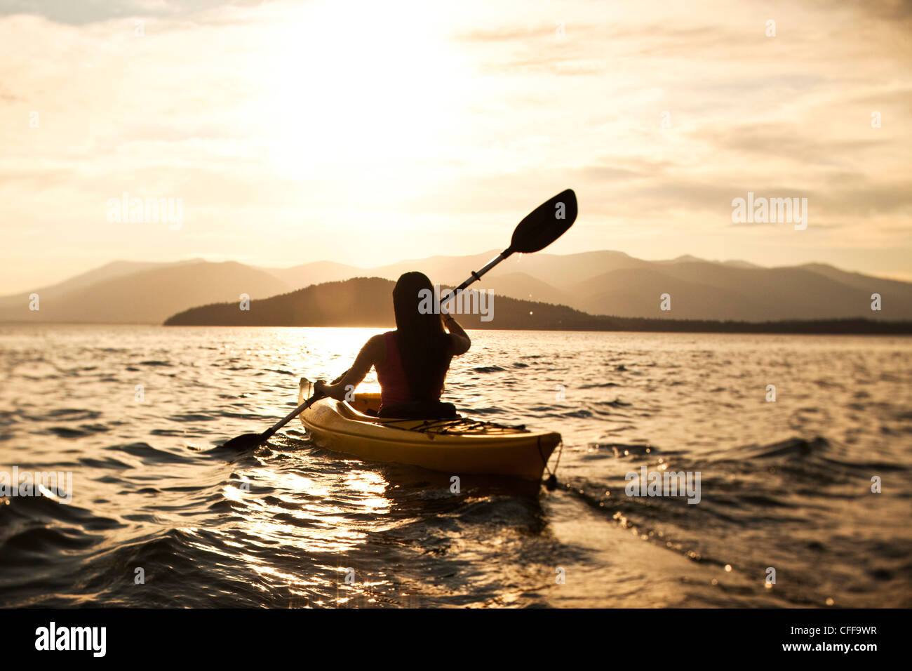 A happy athletic woman kayaking at sunset on a lake in Idaho. - Stock Image