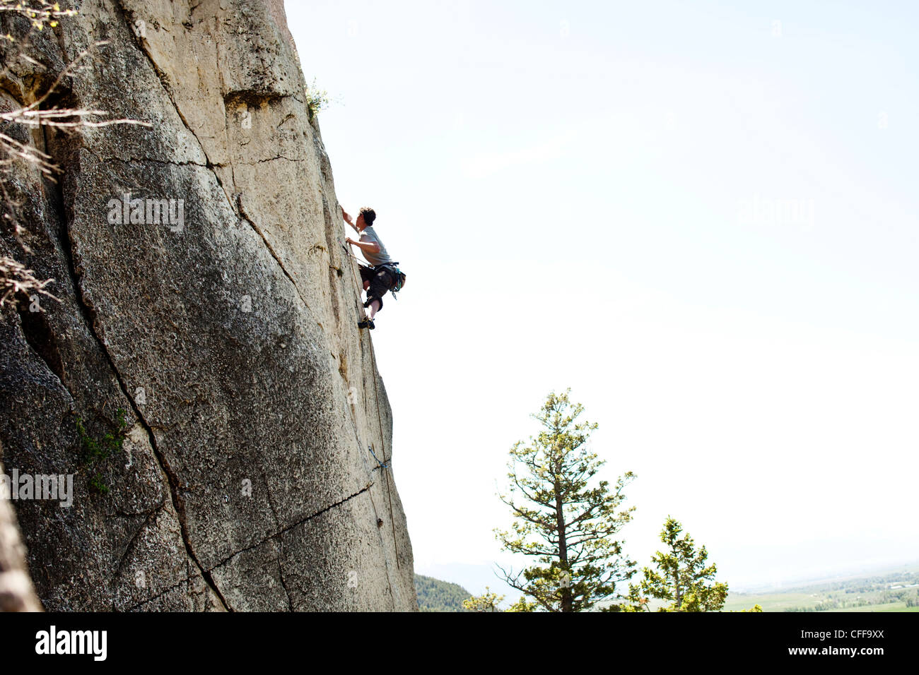 A athletic man rock climbing high off the ground in Montana. - Stock Image