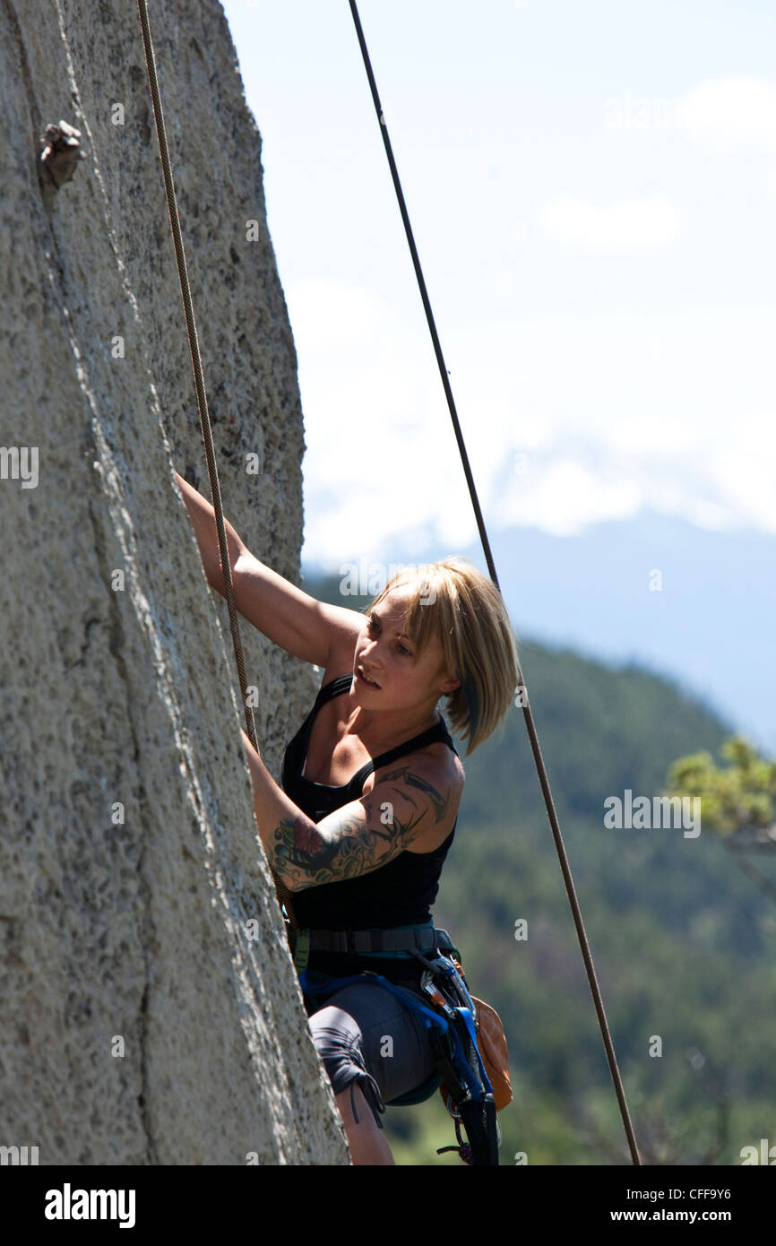 A athletic woman rock climbing high off the ground in Montana. - Stock Image