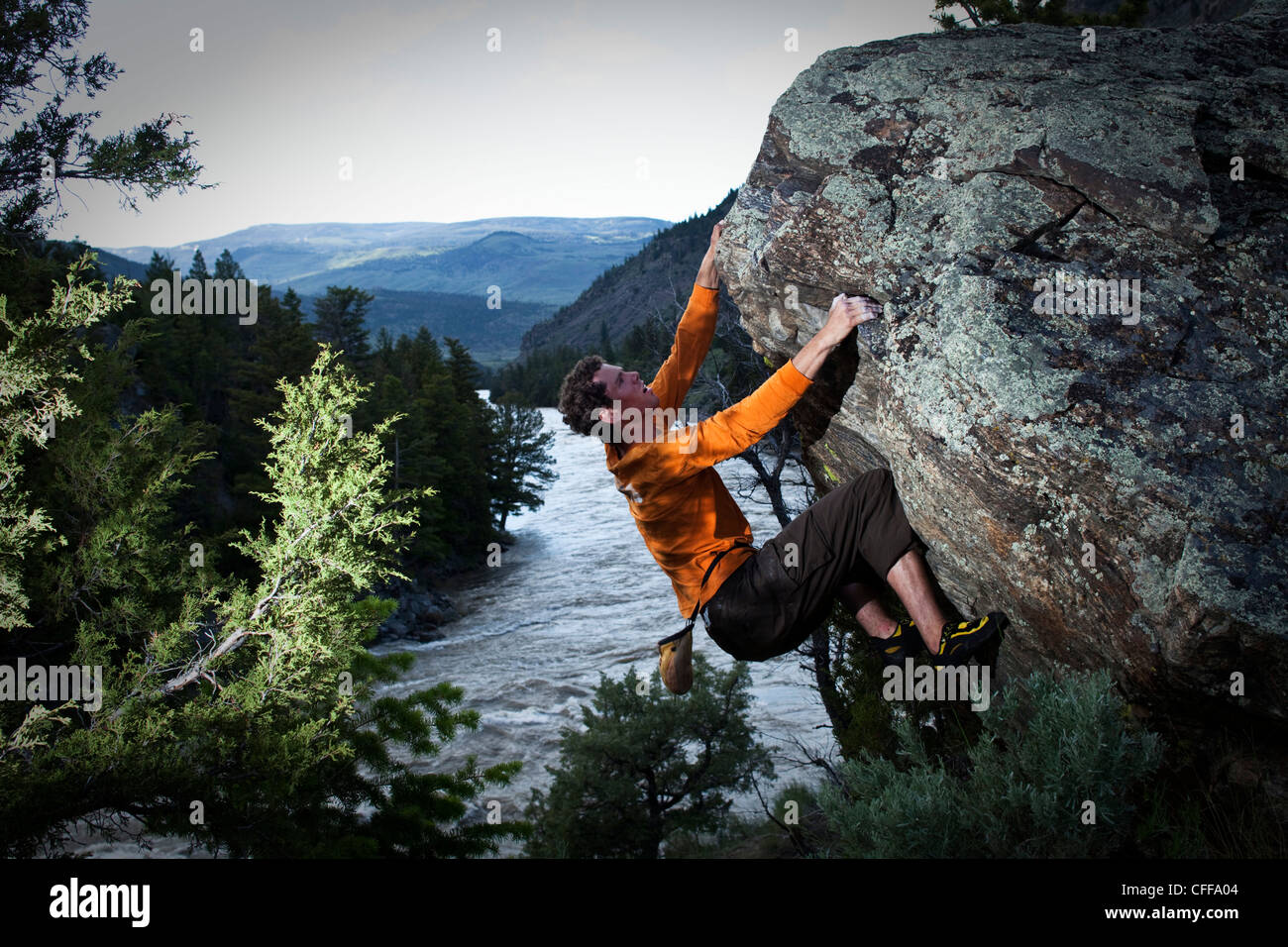 A athletic man bouldering above a river in Montana. - Stock Image