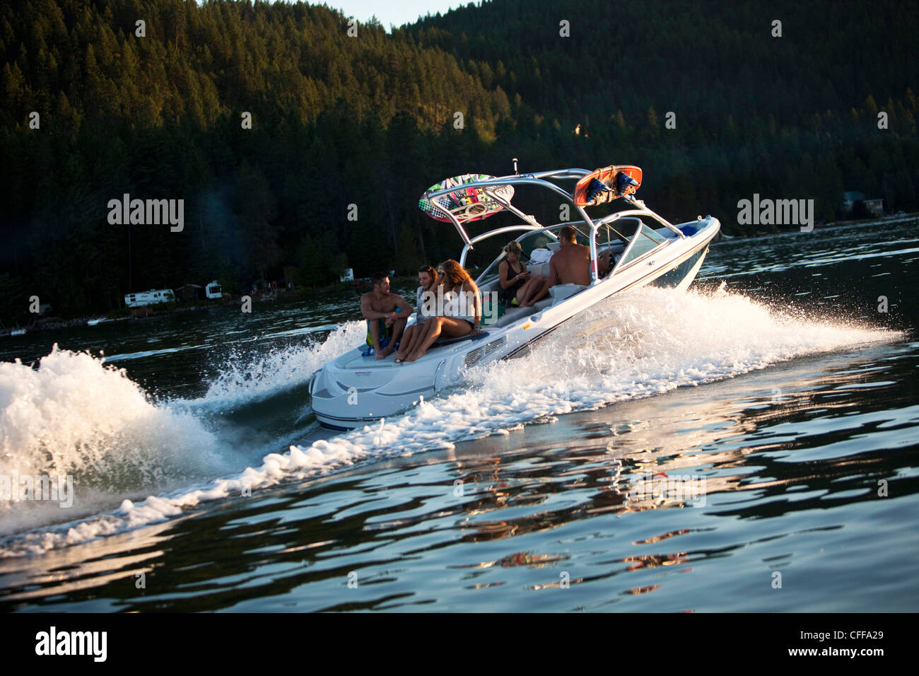 A group of young adults smile while cruising on a wakeboard boat a lake at sunset in Idaho. - Stock Image