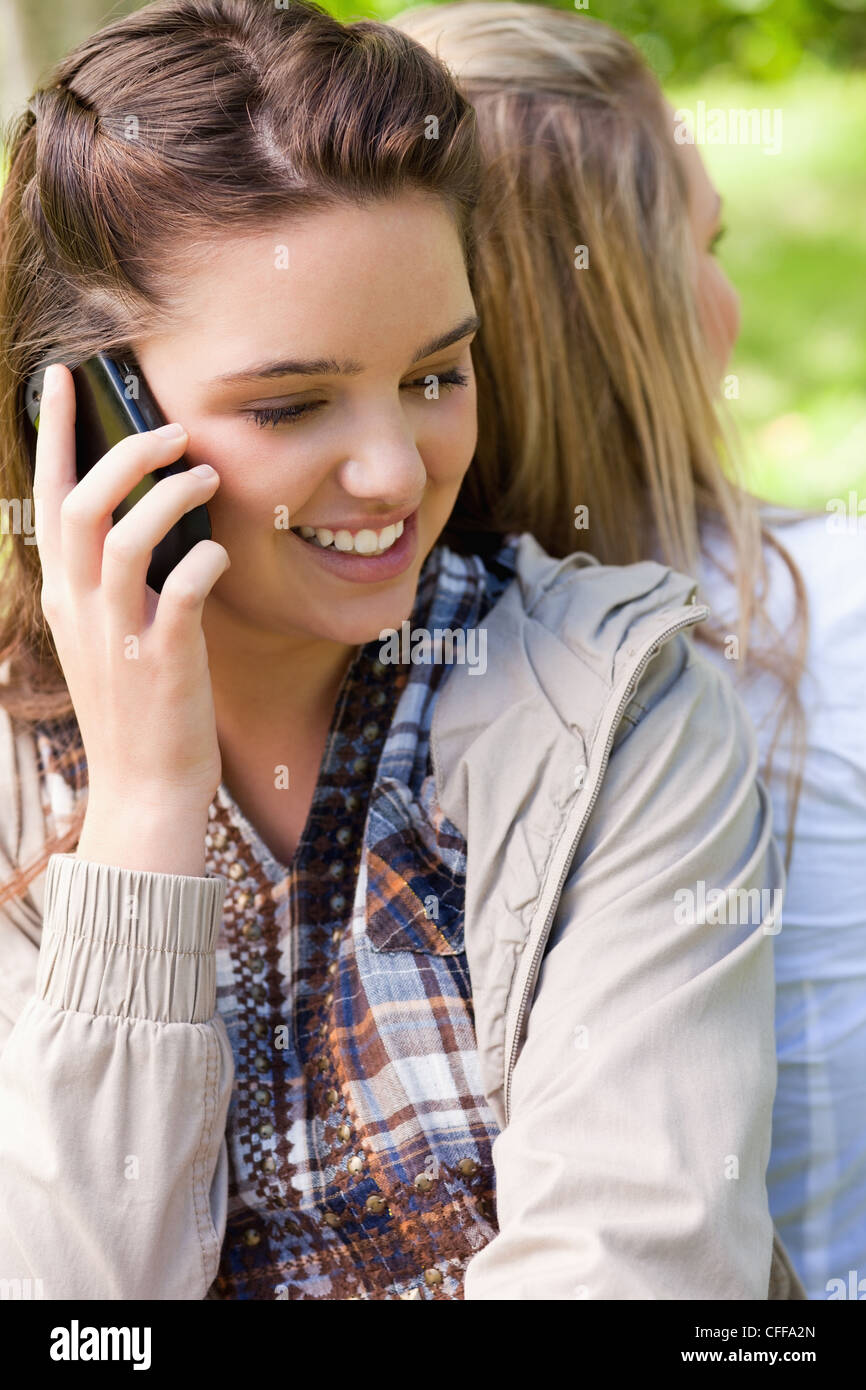 Young smiling girl talking on the phone while being accompanied by a friend - Stock Image