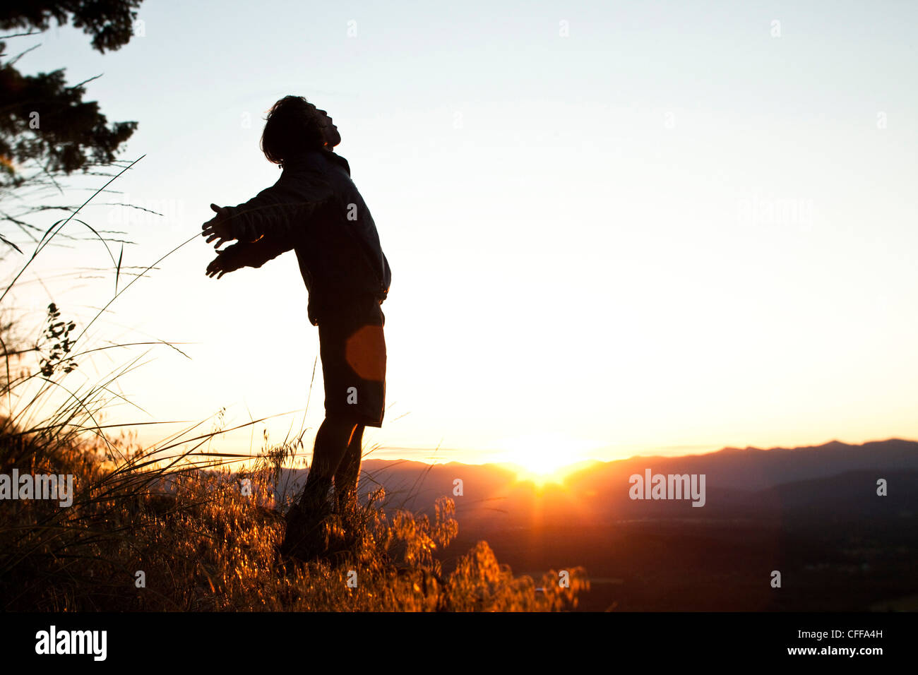 A young man greets the morning on a hiking trip as the sunrises over a valley in Idaho. - Stock Image