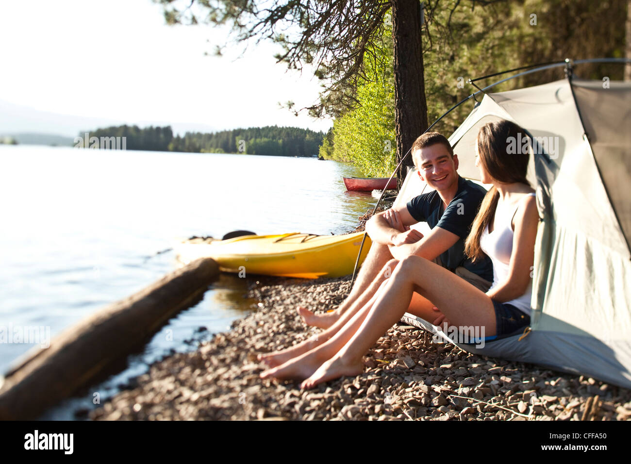 Two young adults laugh and smile on a camping and kayaking trip in Idaho. Stock Photo