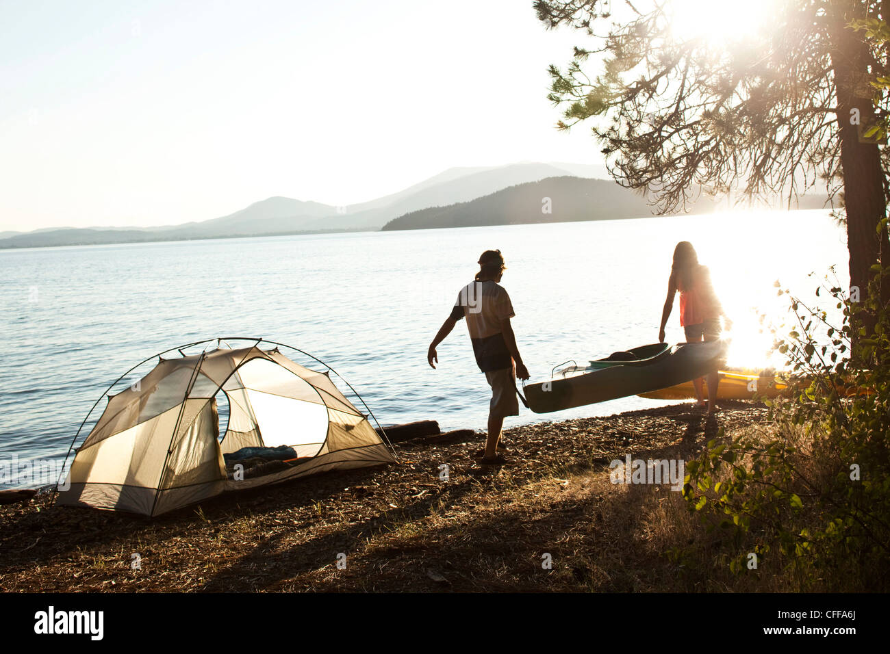 Two young adults carrying a kayak past their camping site next to a lake in Idaho. - Stock Image