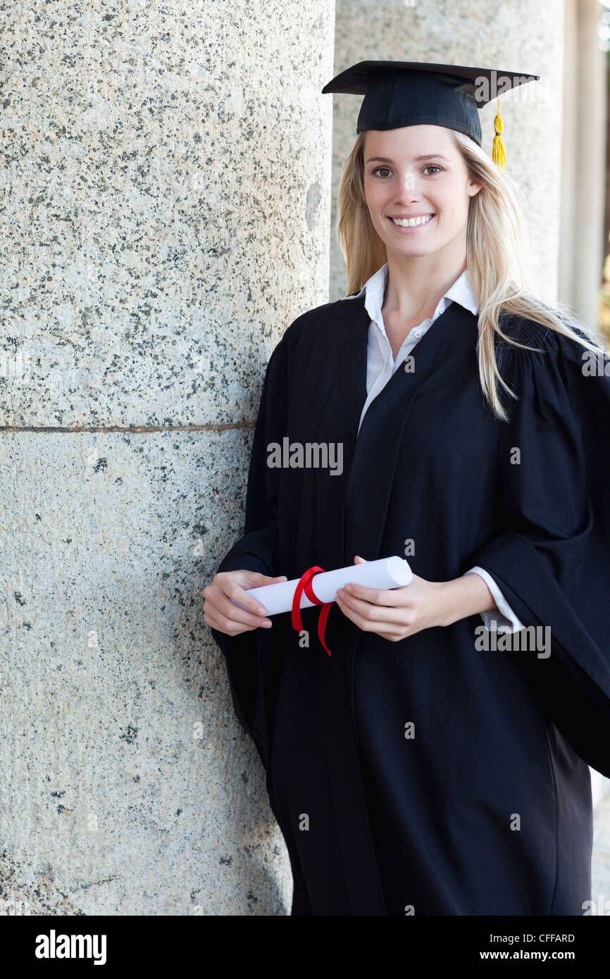 Young smiling graduating student holding her diploma - Stock Image