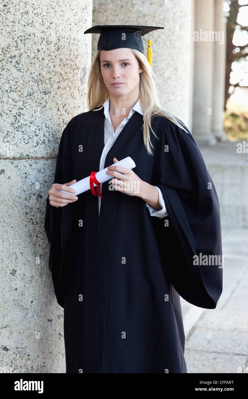Young serious graduating student holding her diploma - Stock Image