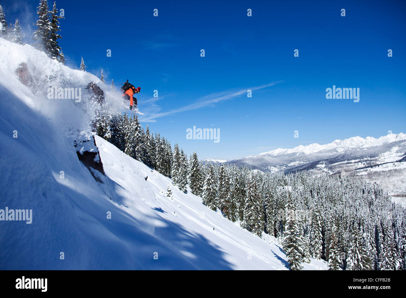 A athletic snowboarder jumping off a cliff on a sunny powder day in Colorado. - Stock Image
