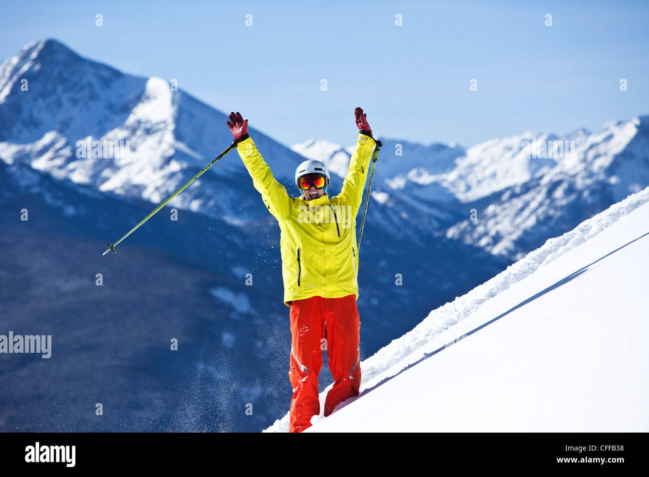 A happy skier smiling raises his arms in celebration of fresh snow with huge mountains behind him in Colorado. Stock Photo